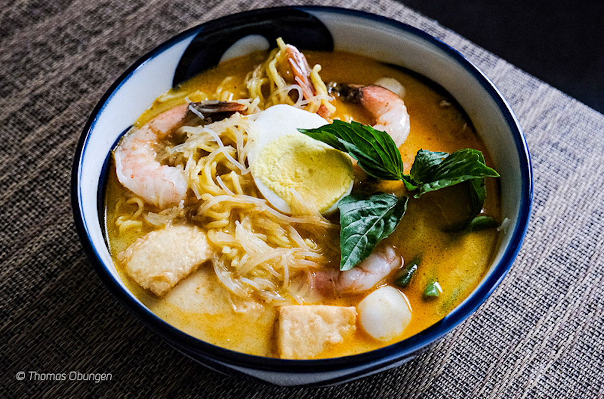 loaded bowl of laksa noodle soup with shrimp, herbs, egg and more