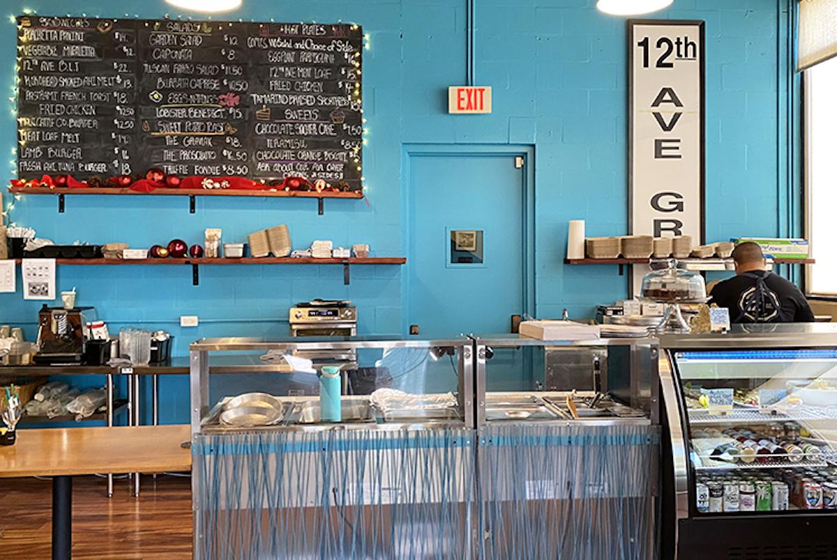 deli cases and a blackboard menu at a sunlit cafe