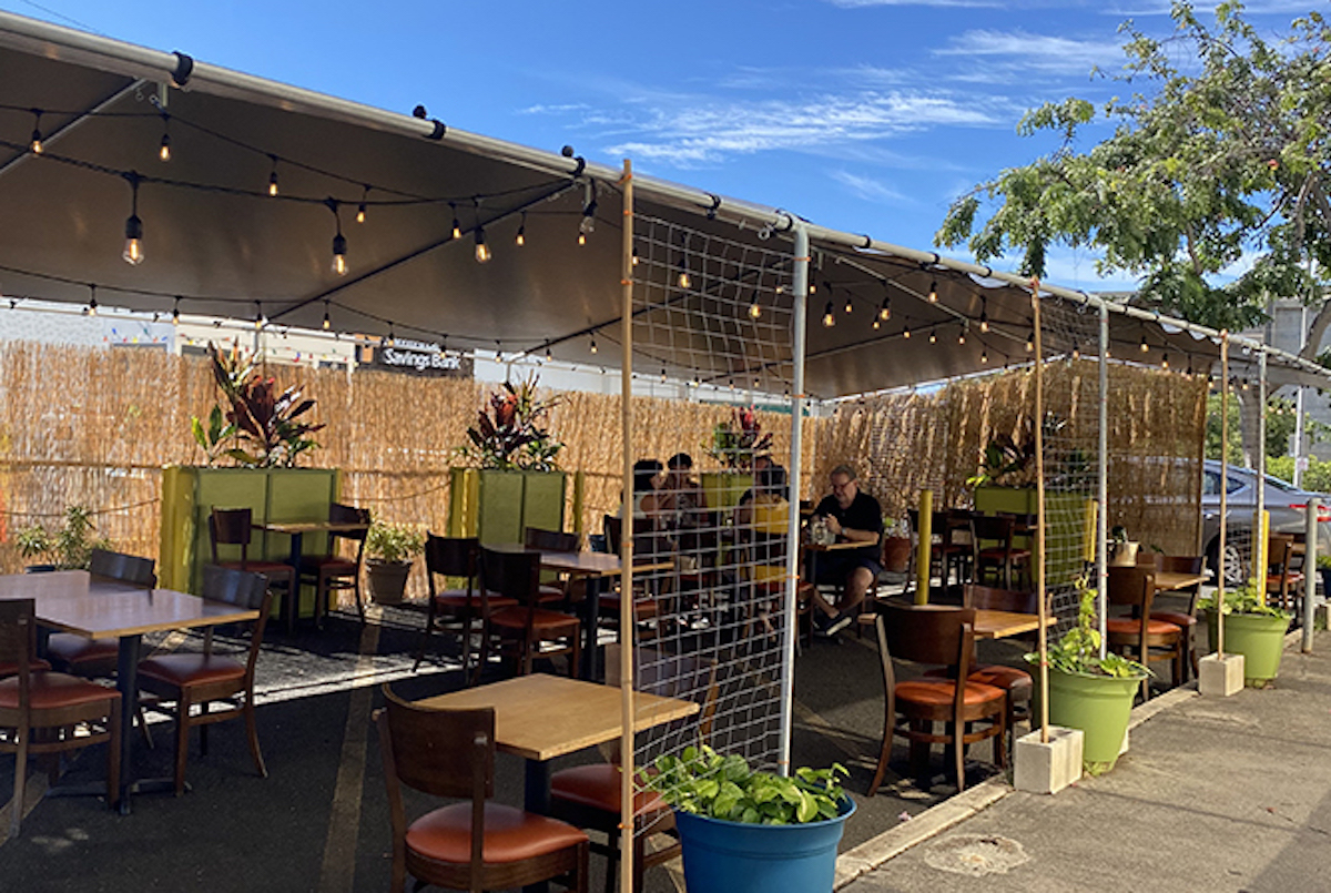 a shady awning and reed fencing protect outdoor tables and chairs