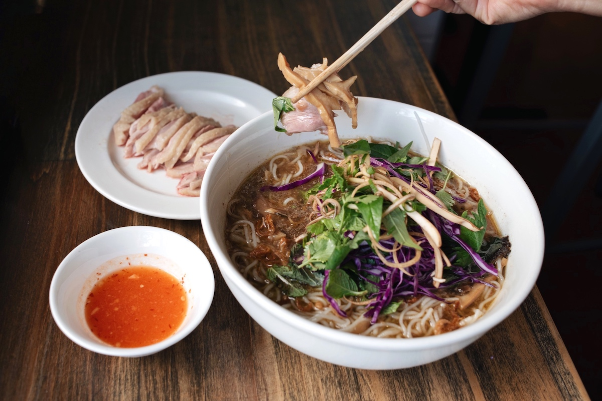 chopsticks holding slivers of duck breast and bamboo shoots hover over a bowl of bun mang vit noodle soup