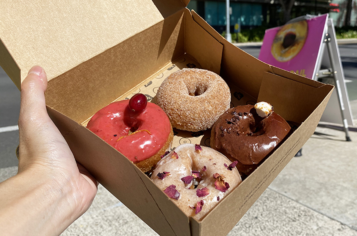 a box holds red, sugar-dusted, chocolate and pink-glazed taro doughnuts