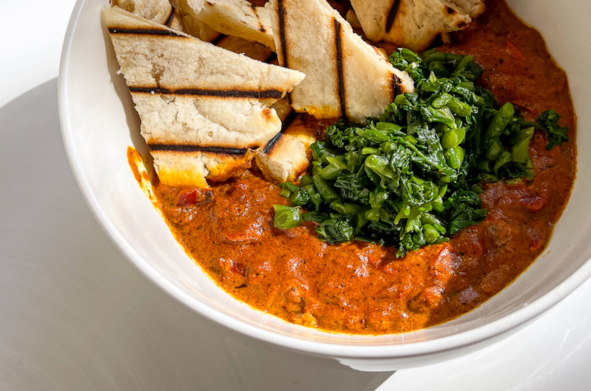 vibrant bowl of tikka masala rimmed with grilled naan slices