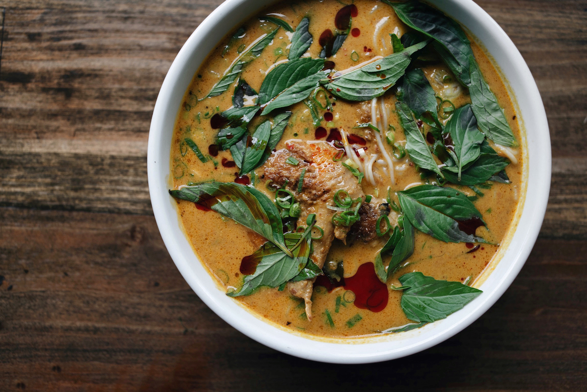 fresh basil leaves top a bowl of rich, turmeric-yellow curry noodles with chicken