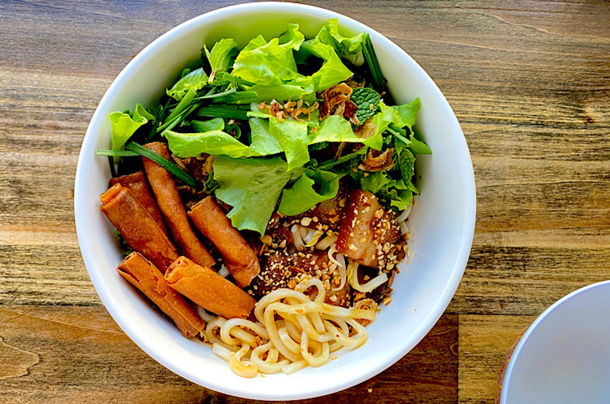 fresh greens, crunchy lumpia wrapper rolls and pork nestle atop udon in a bowl iof cao lau vietnamese noodles