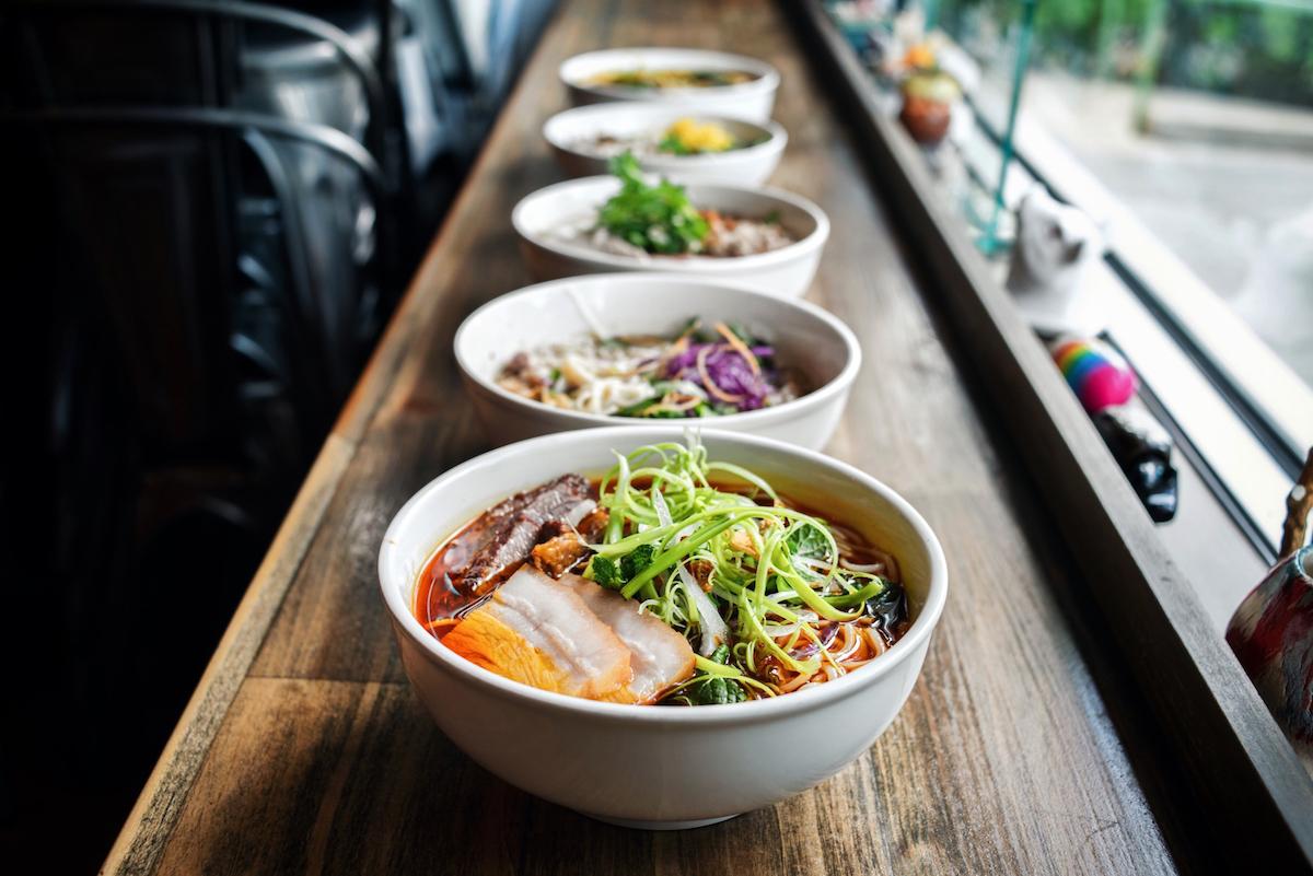 Colorful bowls of different noodle soups line a sunlit counter