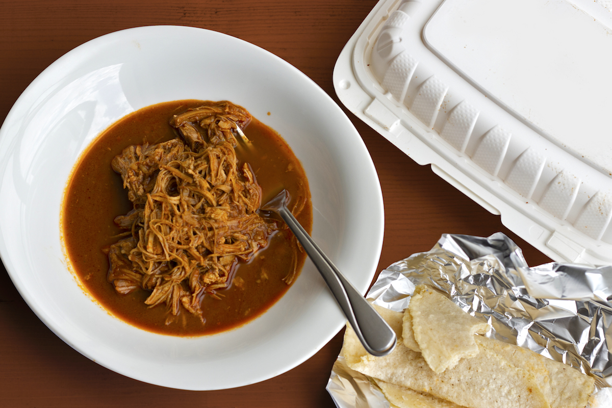 a bowl of shredded chicken surrounded by a sea of deeply red-brown mole sauce with a side of soft tortillas