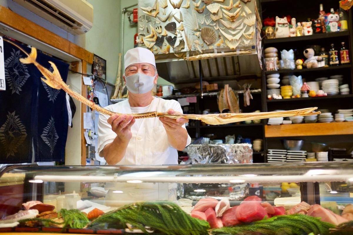 maguroya chef-owner goro obara holds aloft a massive ahi bigeye tuna skeleton