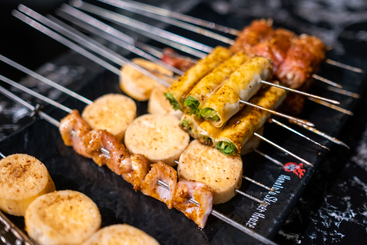 assorted skewers of vegetables and meat cook on a tabletop grill