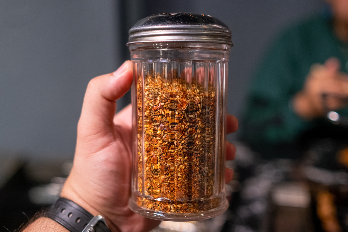 glass shaker holds fiery-looking assortment of dried chiles and chile seeds