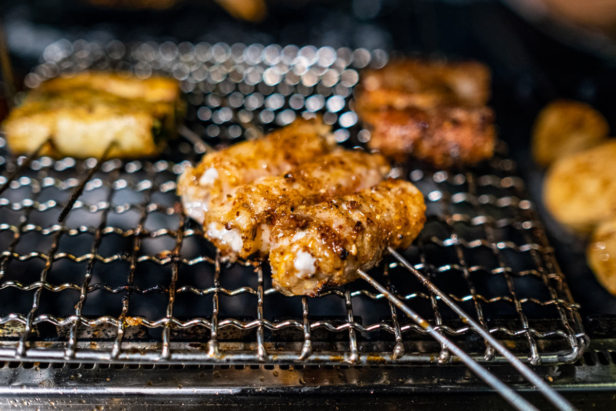 double-skewered rolls of meats, vegetables and mushrooms cook to glistening brown doneness on a grill