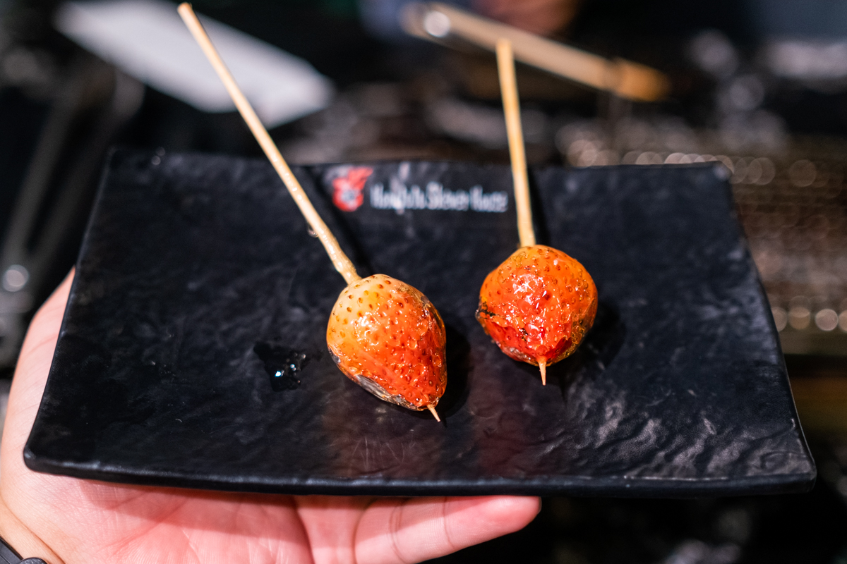 two skewers each hold a pretty grilled candied strawberry