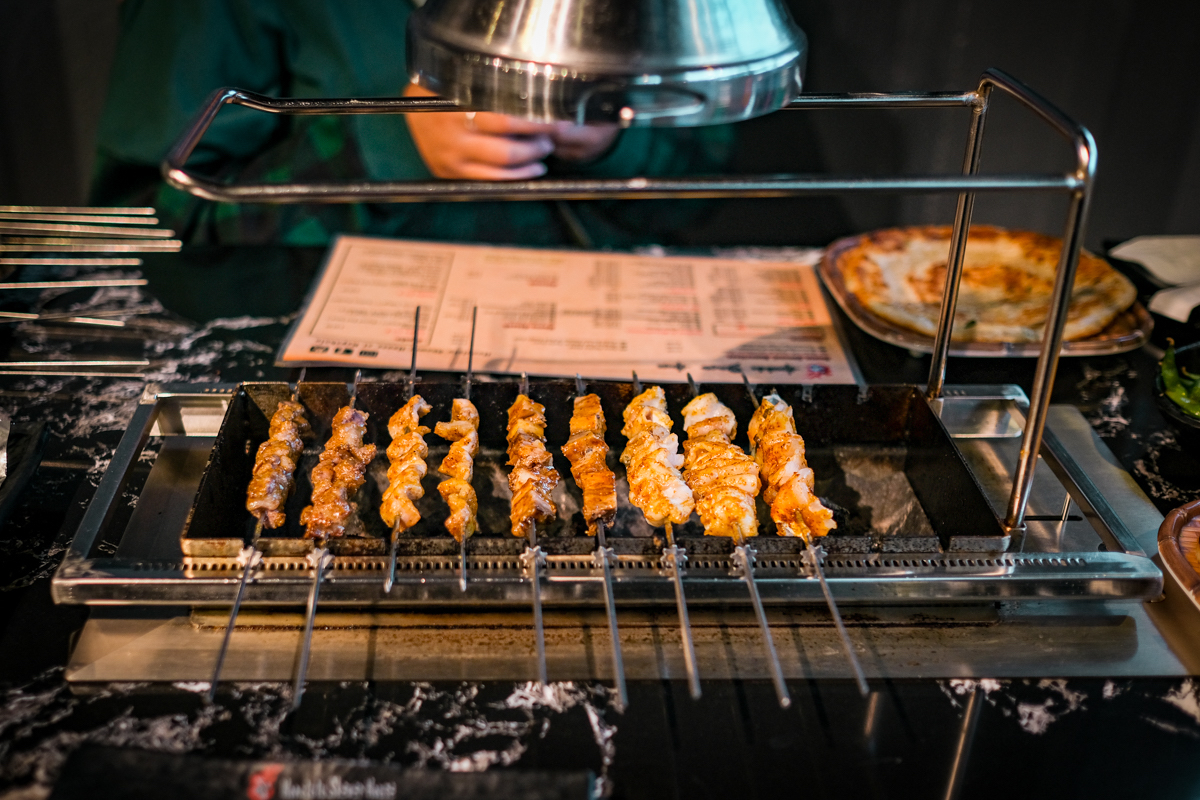 a tabletop grill holds self-rotating skewers of chinese-style barbecued meat