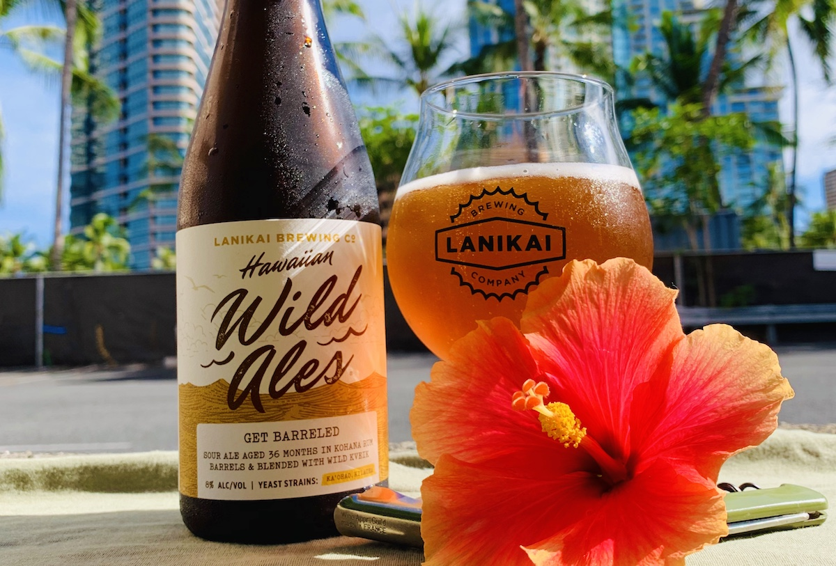 a bottle of Lanikai brewing co. wild ale stands next to a goblet of beer with a red hibiscus in the foreground