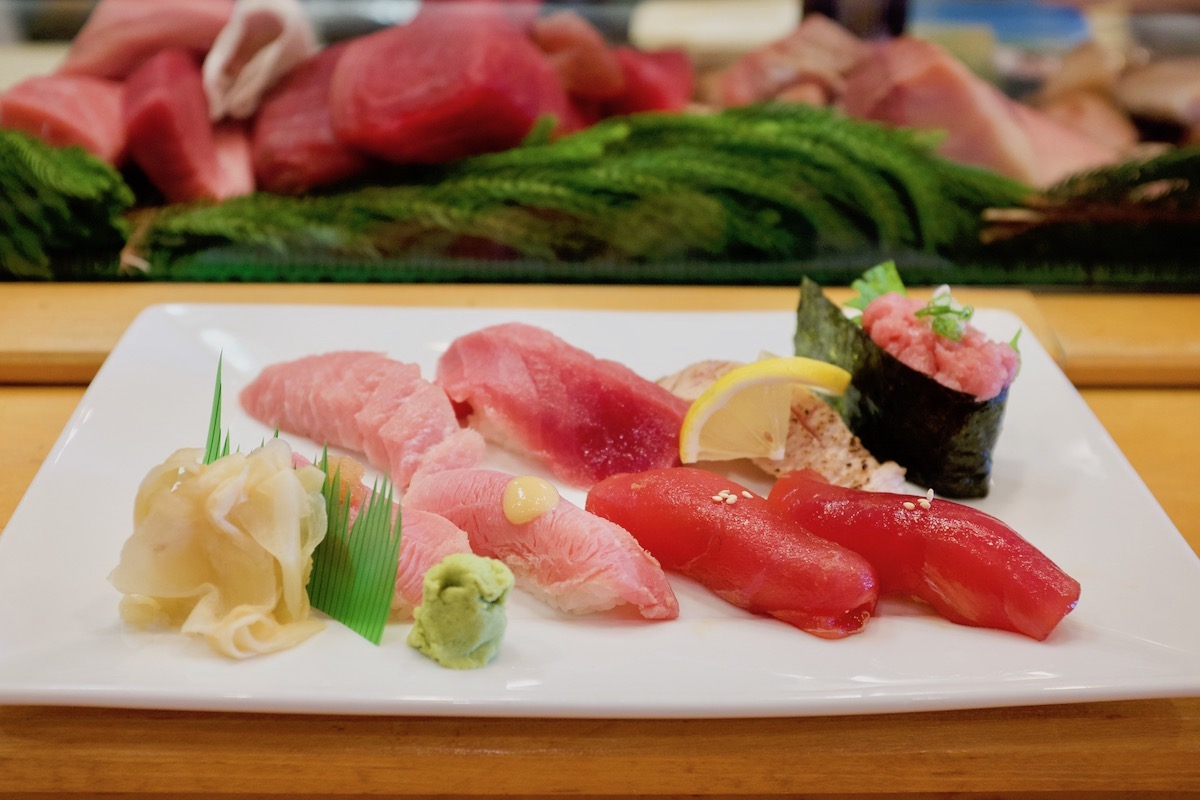 white platter holds different cuts of big eye tuna nigiri sushi, prepared different ways