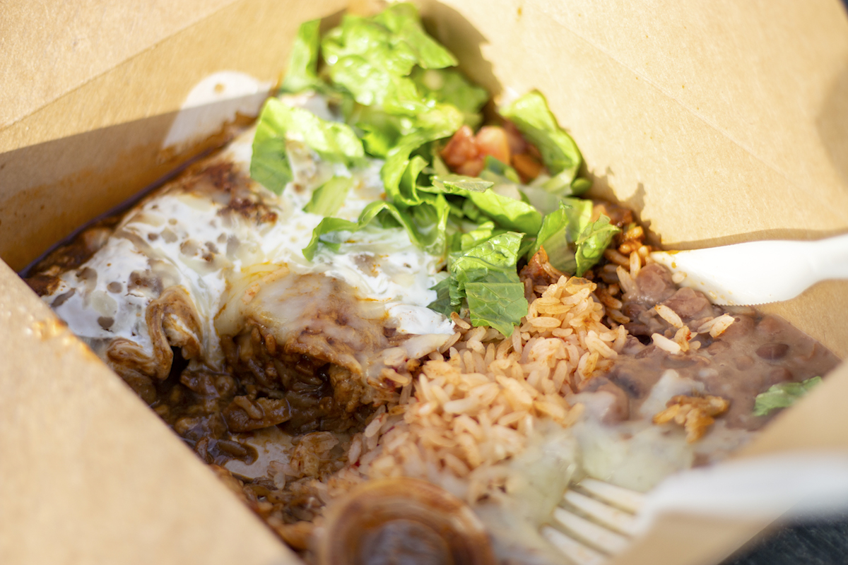 enchilada with mole sauce nestles in a takeout container with salad, rice and beans
