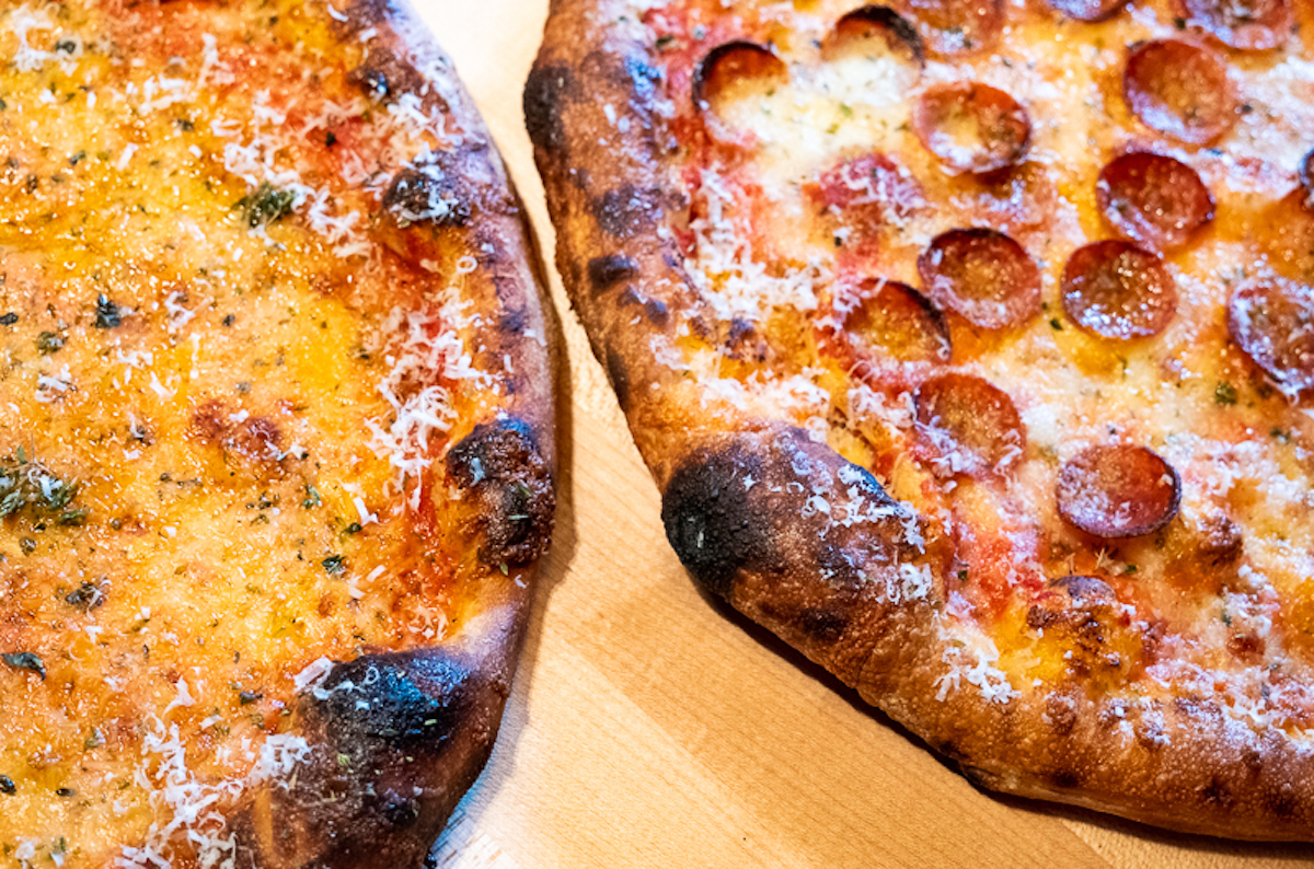 close-up of two cheesy brooklyn-style pizza pies