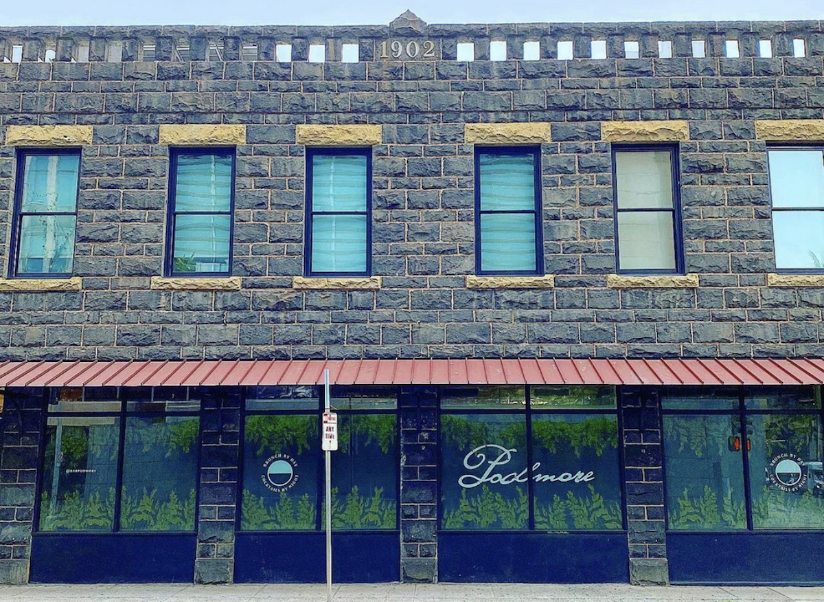 histori two-story lava rock building with bar podmore painted across windows on ground floor