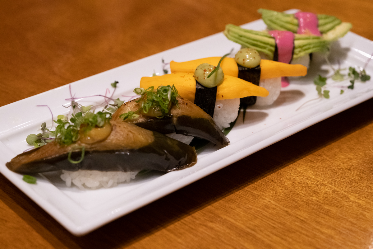 an assortment of vegan nigiri sushi: eggplant, pickled mango, avocado