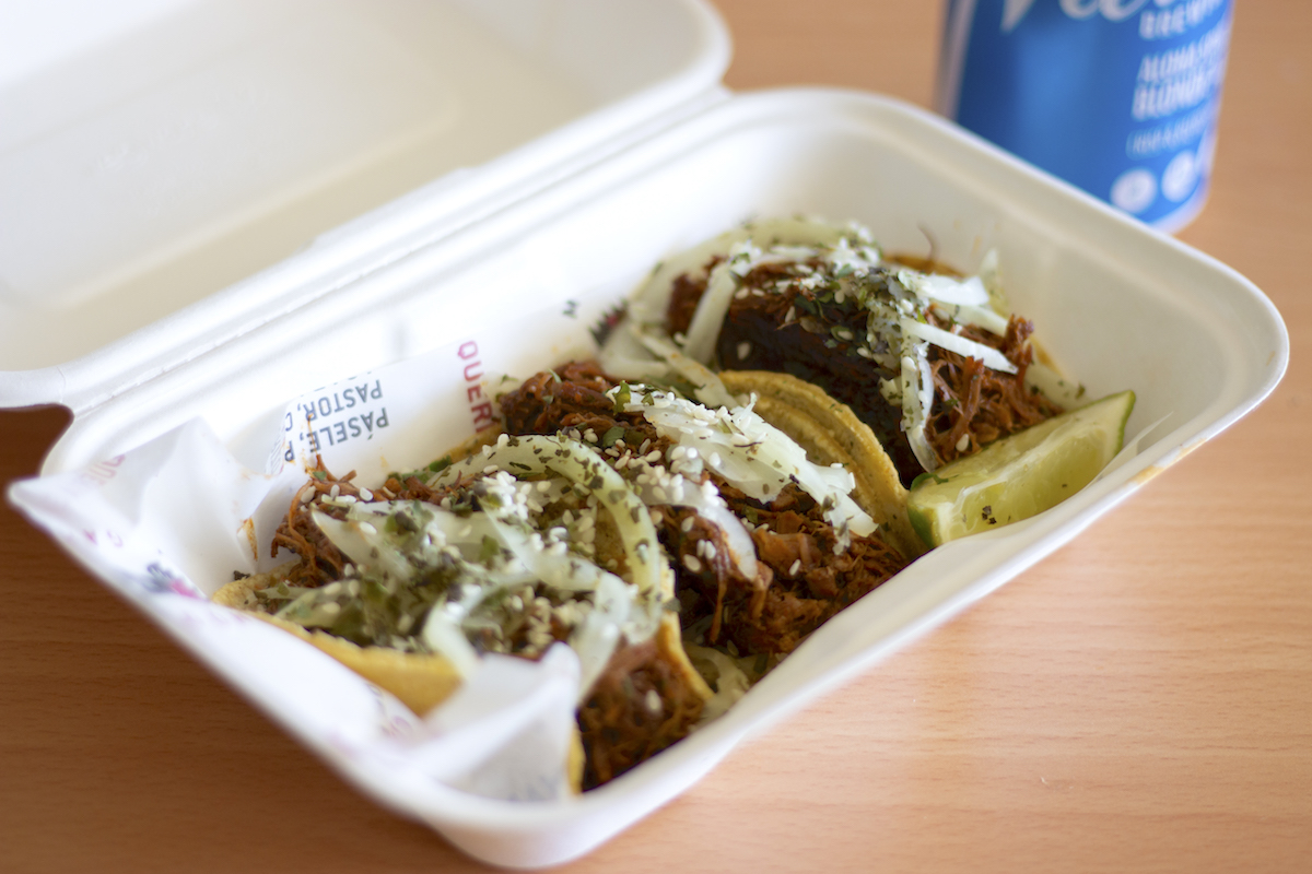 a trio of street tacos topped with mole sauce and fresh onions