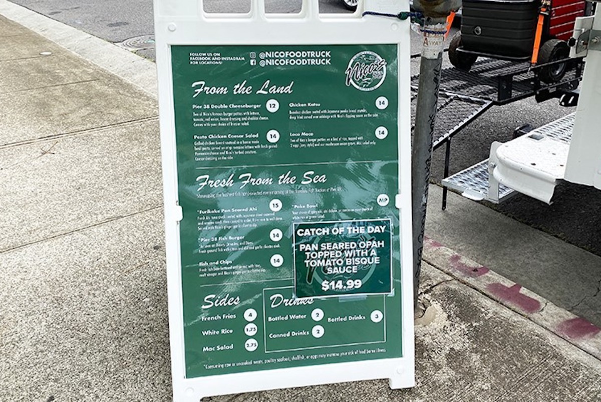 sidewalk menu shows land and sea plate lunches at nico's food truck