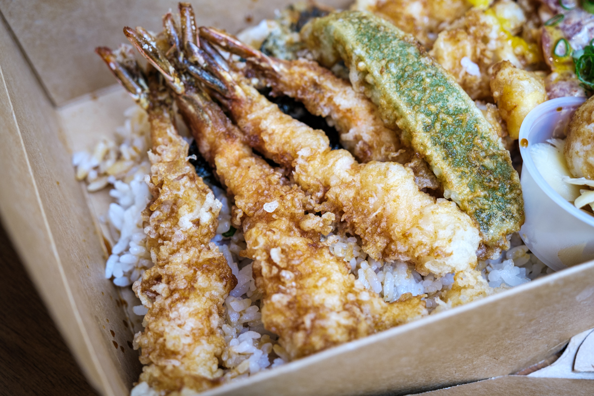 closeup of 4 shrimp tempura atop rice in a takeout box