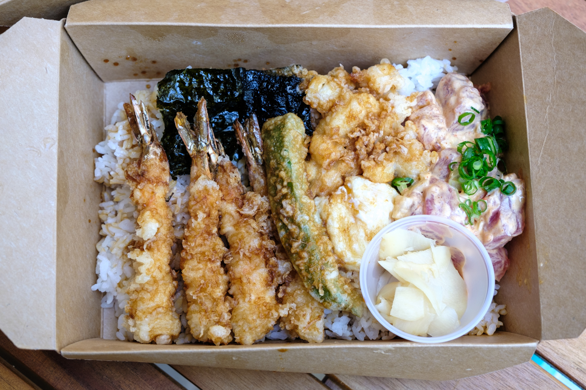 view of 4 shrimp tempura with assorted other tempura and poke in a takeout container