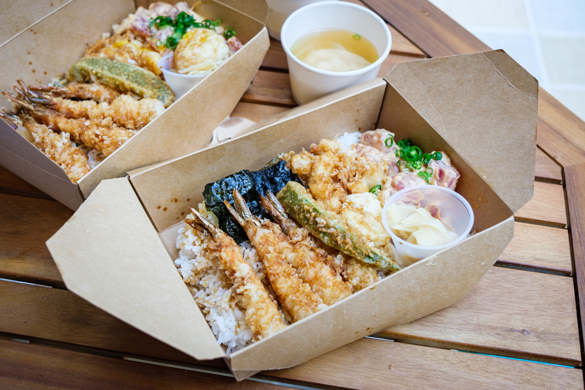 identical takeout boxes of shrimp tempura bowls come with assorted sides and miso soup