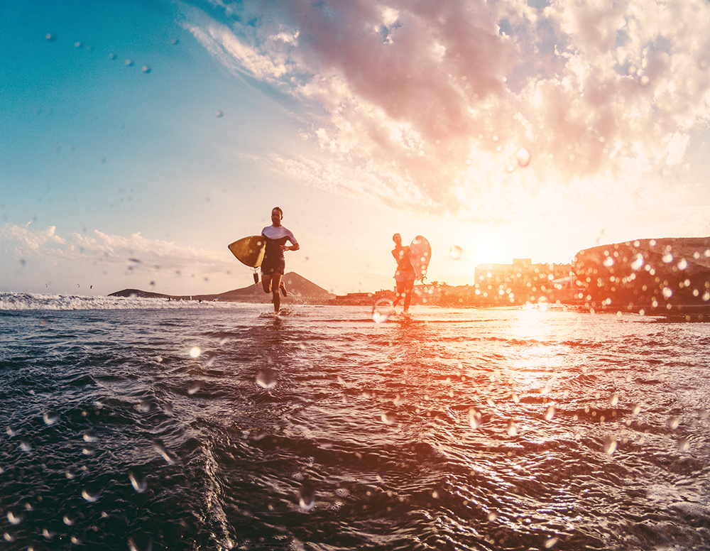 Happy Urfers Running With Surf Boards On The Beach Sporty People Having Fun In Sunny Day Extreme Sport, Travel And Vacation Concept Focus On Bodies Silhouettes Water On Camera Lens